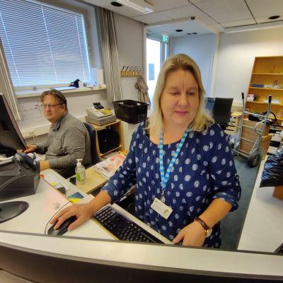 Anne Nylund och Matts Mannström betjänar vid lånedesken i Karis bibliotek i Grabbegården.