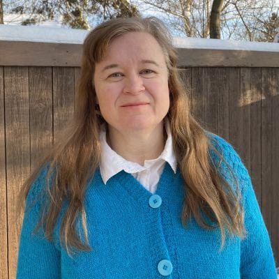 En kvinna med långt hår och turkos, stickad tröja står ute i vinterlandskap.