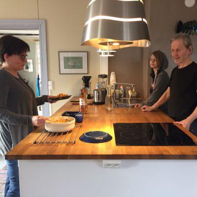 tre personer kring en köksö.