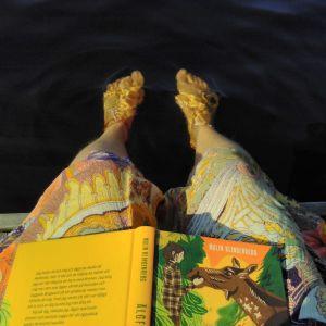 Person har fötter i vattnet och en bok i knät.