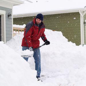 En man skyfflar snö utanför en villa.