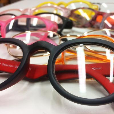 Erilaisia silmälaseja pöydällä.