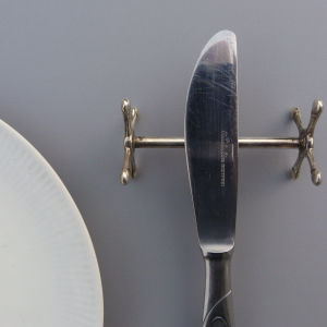 Närbild på en matkniv med eggen vänd inåt mot tallriken.