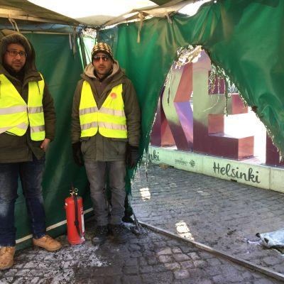 Två män står vid ett hål i tältet som brunnit