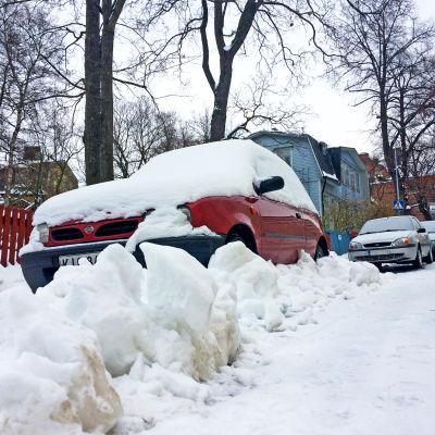 Autoja kadun varressa lumikinoksen alla.
