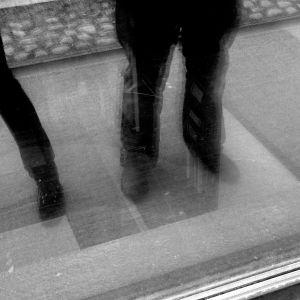 Reflektionen av ett benpar och ett ensamt ben i ett fönster