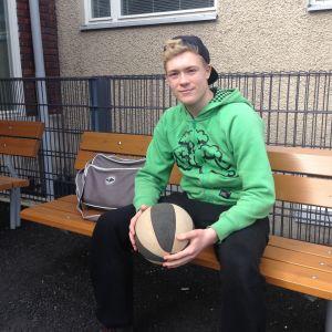 En pojke som sitter på en bänk utanför skolan med en basketboll i handen.