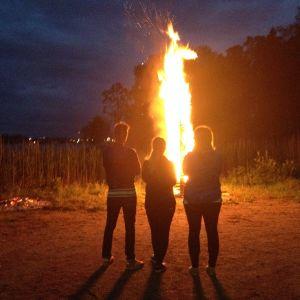 Kristine Andora Nilsen, Elisabeth Gjestland och Jontti Granbacka betraktar midsommarbrasan på Fölisön