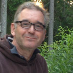 silmälasipäinen mies metsikössä