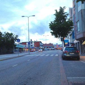 En gata i en stads centrum, sommarkväll, några bilar syns, affärer, övergångsställe, mittrefuge, släckta gatulyktor