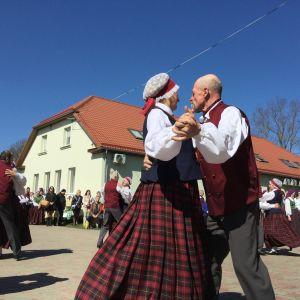 Ett folkdanspar i förgrunden och fler dansande par i bakgrunden