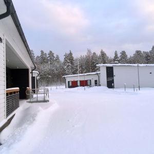 Byggnad med vit och mörgrå träfasad. Veranda med ramp för rullstol. Flera vita byggnader i bakgrunden.