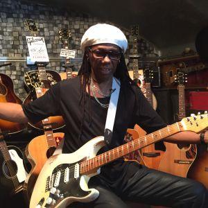 Kitaristi Nile Rodgers istuu kitaroidensa keskellä.