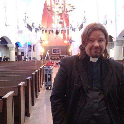 Präst med långt hår i kyrka