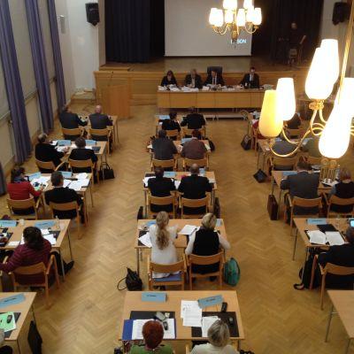 En sal med människor som sitter två och två vid bord.