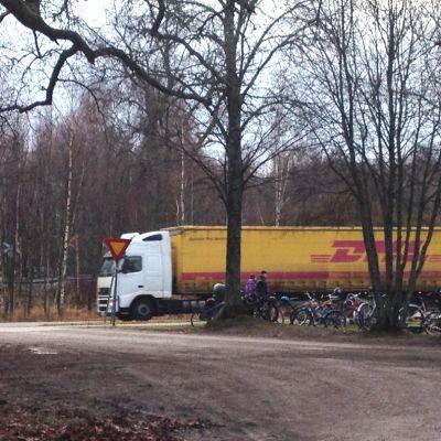En stor lastbil kör förbi en plats där många cyklar står parkerade. Triangeltrafikmärke syns.