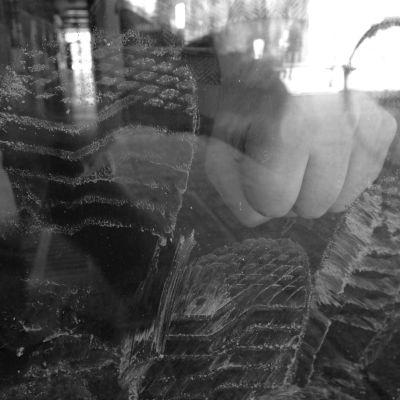 Knytnäve mot fönsterglas med reflektioner av cykel. I bakgrunden korridor