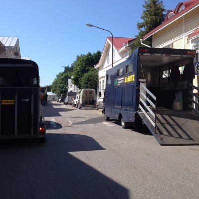 Flera hästtransportbilar som står parkerade på båda sidan av gatan med gamla trävillor. sommar, sol.