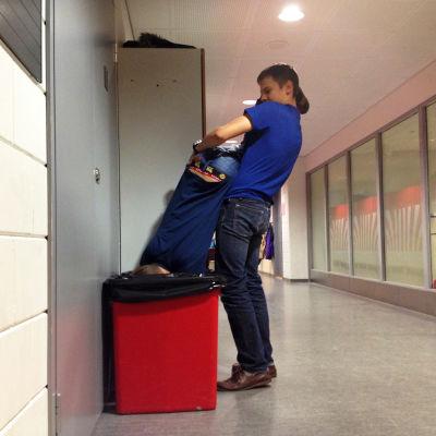 En pojke tvingar ner en annan i en sophink i skolans korridor.