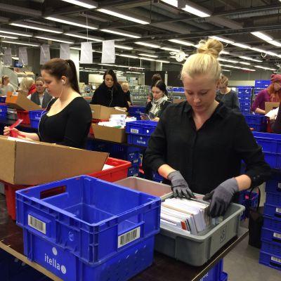 Emma Kauppila (t.h.) sorterar julhälsningar på sorteringscentralen.