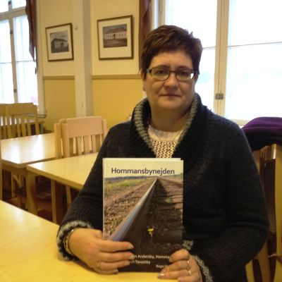 """Viola Malmberg, sekreterare i föreningen Fyra byar NOAK, med boken """"Hommansbynejden som vi minns den"""""""