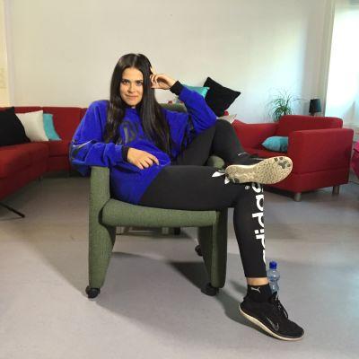 Sara istuu tuolissa ja hymyilee kameralle.