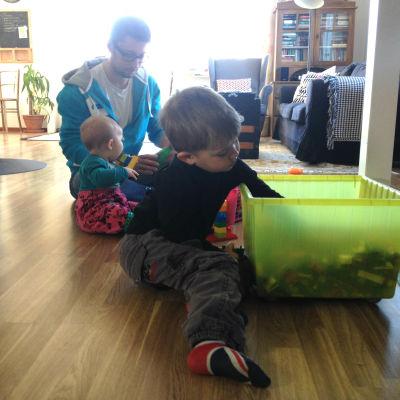 Marcus Jungersten (i bakgrunden) bygger lego med sina barn Elvina och Ebbe.