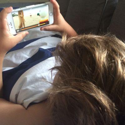 Pojke tittar på BUU-klubben på mobiltelefon