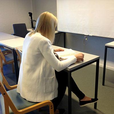 Kvinna studerar en bok vid ett bord