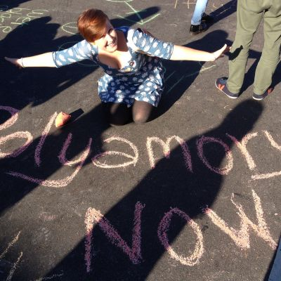 Texten Polyamory now står skrivet med krita på asfalt.