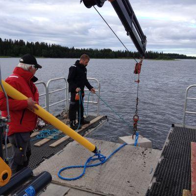 Daniel Sundvik (i rött) och Simon Näsman gör sig redo att sänka ner betonklossen och remmaren.