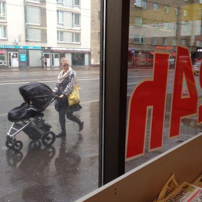 barnvagn utanför affär med 24h skylt.