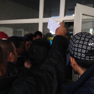 Asylsökande tränger utanför Åbo polisstation.