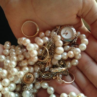 smycken, pärlor, guldringar, armband med mera i en salig röra