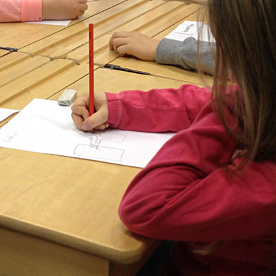 Flicka ritar på ett papper vid en pulpet