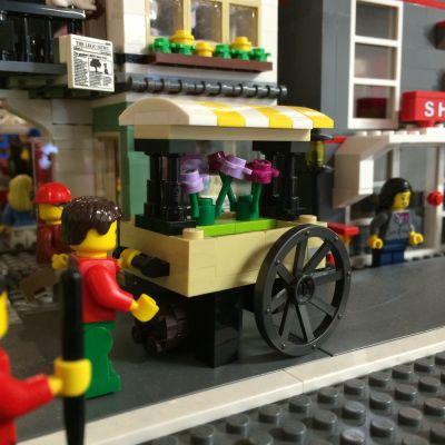 Lego-figur som håller i en vagn med blommor.