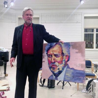 Mårten Johansson håller i en tavla som föreställer honom själv.