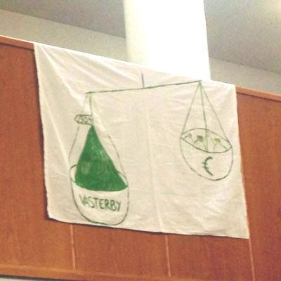 En flagga där någon ritat en väg och på den ena vågskålen står det Västerby och på den andra ett eurotecken.