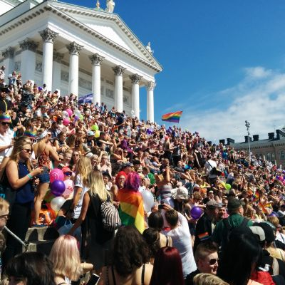 Trapporna till Helsingfros domkyrka på Senatstorget är fullsatta av pridedeltagare med regnbågsflaggor och ballonger.
