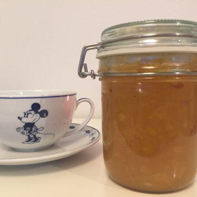 Valkoinen teekuppi ja marmeladipurkki valkoisella pöydällä.