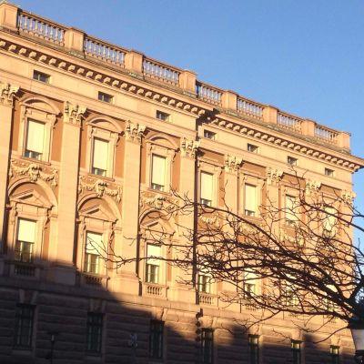 Utomhusbild på en flygel av riksdagshuset, Stockholm. Blå himmel, sol, träd i förgrunden utan blad.