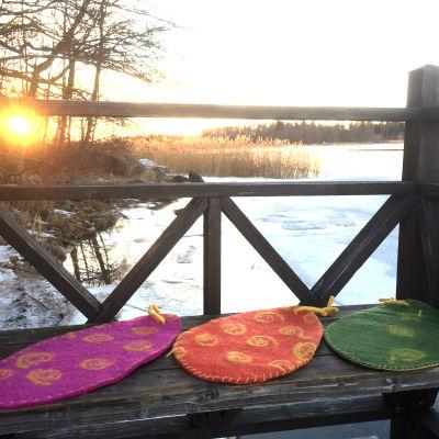 Tre tovade sittunderlag på en bänk med soluppgång i bakgrunden.