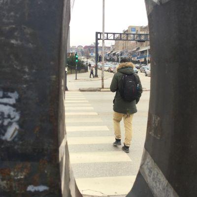 En ung man går över gatan, fotad genom en springa så att han ser inklämd ut