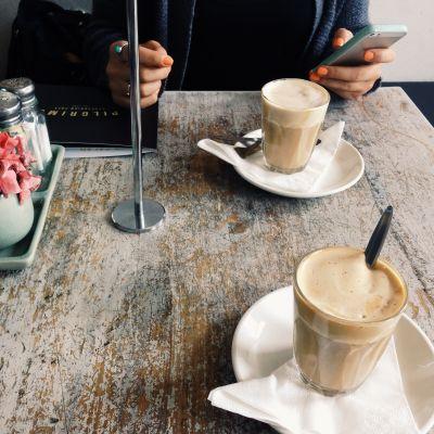 Två koppar kaffe på bordet i ett kafée och en kvinnohand som håller i en mobiltelefon.