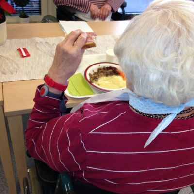 Äldre person äter.