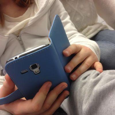 Närbild på en mobiltelefon som ett barn håller i.
