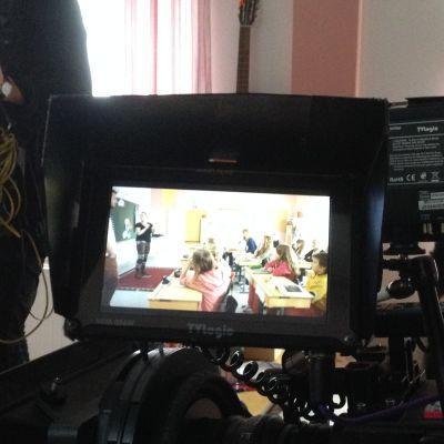 skolbarn vid plupeter syns i en tv-kameras lilla skärm i ett klassrum.