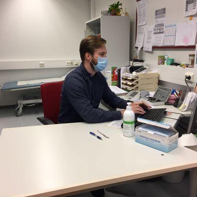 Lääkäri istuu vastaanotolla tietokoneen äärellä maski kasvoilla