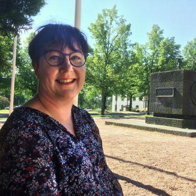 Työnohjaaja Anu Ojanperä istuu puistossa.