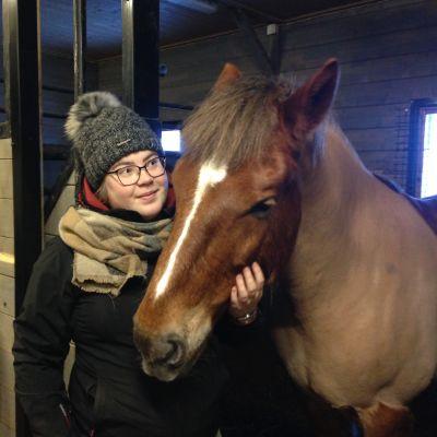 En kvinna står bredvid en häst i ett stall. Hon håller handen runt hästens mule.